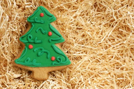 Christmas gingerbread cookie made in the shape of a Christmas tree on a paper shaving photo
