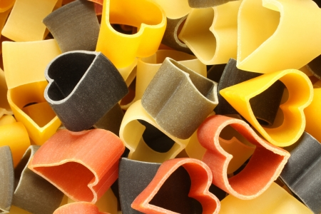 Heart-shaped colored Italian pasta, for backgrounds or textures on a white background photo
