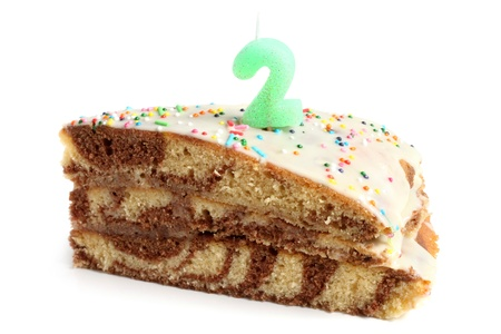 Slice of birthday cake with number two candle on a white background photo
