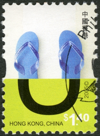 HONG KONG, CHINA - CIRCA 2005: A stamp printed in Hong Kong, China shows Letter of the Alphabet - U-sandals, series Upper half of letters made with common household items, circa 2005 photo