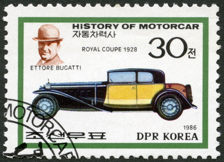 NORTH KOREA - CIRCA 1986: A stamp printed in North Korea shows Ettore Bugatti and Royal coupe, 1928, series History of the Motor Car, circa 1986 photo