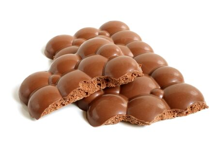 honeycombed: Porous chocolate pieces on a white background Stock Photo