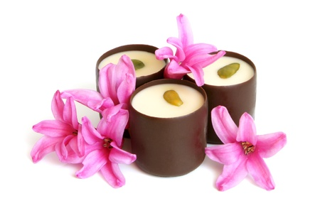Chocolate sweets with pink flowers of hyacinth on a white background photo