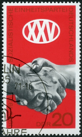 postal card: GERMANY- CIRCA 1971  A stamp printed in Germany shows Clasped Hands, 25th anniversary of Socialist Unity Party of Germany  SED , circa 1971