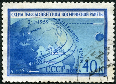 USSR - CIRCA 1959: A stamp printed in USSR shows Globe and route of Luna 1, the scheme of a line of the Soviet space rocket on an earth surface, circa 1959 photo