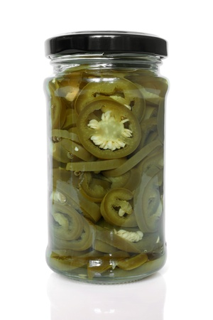 jalapeno pepper: Slices of preserved Jalapeno pepper in glass jar on a white background