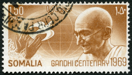 nonviolent: SOMALIA - CIRCA 1969: A stamp printed in Somalia shows portrait of Mohandas Karamchand Gandhi (1869-1948), globe and hands releasing dove, circa 1969