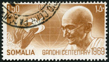 nonviolent: SOMALIA - CIRCA 1969: A stamp printed in Somalia shows portrait of Mohandas Karamchand Gandhi (1869-1948), globe and hands releasing dove, circa 1969