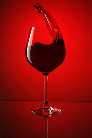 Glass of red wine on red background photo