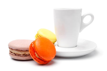 Cup of coffee  with colorful french macaroons on white  photo