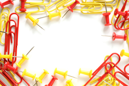 Multicolored paper clips and drawing pins on white background photo