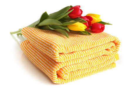 Bath towel with fresh tulips on white background photo