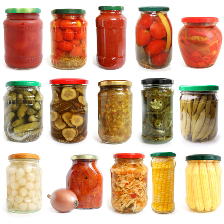 Selection of various vegetables canned in glass jars on white background
