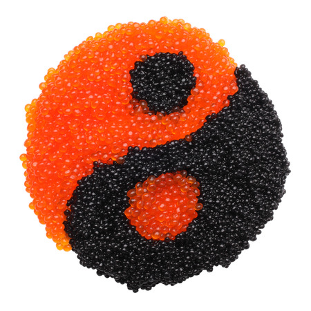 Black and red caviar forming a yin yang symbol isolated on white background photo