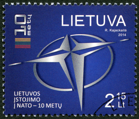 accession: LITHUANIA - CIRCA 2014: A stamp printed in Lithuania showis logo of NATO and a stylized flag of Lithuania, the 10th anniversary of the accession to NATO, circa 2014 Editorial