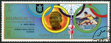 olympiad: AJMAN - CIRCA 1972: A stamp printed in Ajman shows John Akii-Bua (1949-1997), Uganda, series Gold medalists of the Olympic Games, Munich, circa 1972