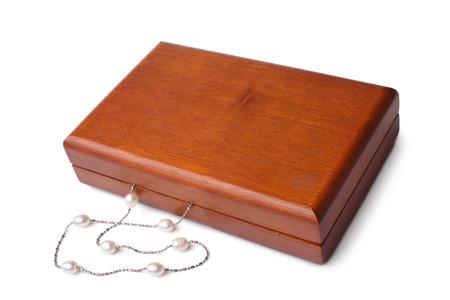 Holzkasten mit Perlenkette auf weißem Hintergrund