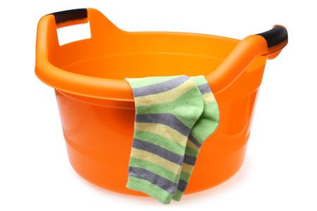 lave: Orange plastic wash bowl with striped socks on white background