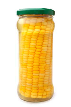 Preserved corn ear in glass jar on white background
