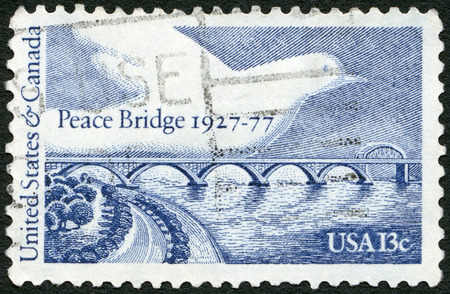 united states postal service: UNITED STATES OF AMERICA - CIRCA 1977: A stamp printed in USA shows Peace Bridge and Dove, dedicated to the 50th anniversary of the Peace Bridge, connecting Buffalo, NY with Fort Erie, Ontario, circa 1977
