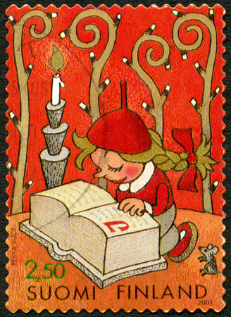 FINLAND - CIRCA 2001: A stamp printed in Finland shows little elf girl with plaited hair reading Santa's thick ABC-book, designed by Pekka Vuori, circa 2001 Éditoriale