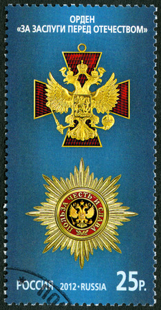 RUSSIA - CIRCA 2012: A stamp printed in Russia shows The Order For Merit to the Fatherland on the blue background, series State awards of the Russian Federation, circa 2012