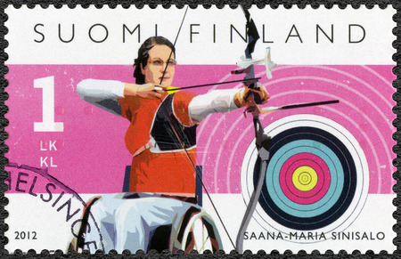 disabled sports: FINLAND - CIRCA 2012: A stamp printed in Finland shows Finnish Champions in disabled sports, para-archer Sanna-Maria Sinisalo, series Summer Paralympic Games, circa 2012