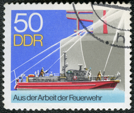 freighter: GERMAN DEMOCRATIC REPUBLIC - CIRCA 1977: A stamp printed in GDR Germany shows Fireboat alongside freighter, series Firemen Activities, circa 1977 Editorial