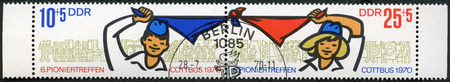 gdr: GERMAN DEMOCRATIC REPUBLIC - CIRCA 1970: A stamp printed in GDR Germany shows Pioneers Boy and Girl Holding and Waving Kerchief and Pioneer Activities, circa 1970