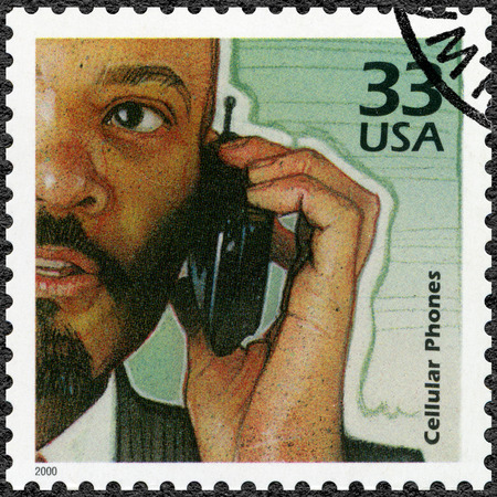 postage: UNITED STATES OF AMERICA - CIRCA 2000: A stamp printed in USA shows Man using mobile phone, increase in use of cellular phones, series Celebrate the Century, 1990s, circa 2000 Editorial