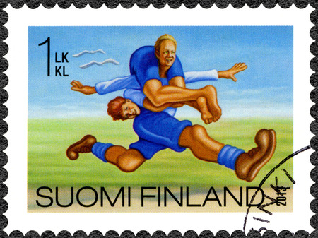 oddity: FINLAND - CIRCA 2013: A stamp printed in Finland shows wife carrying, series Finnish Oddity, circa 2013