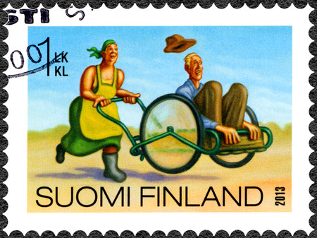 FINLAND - CIRCA 2013: A stamp printed in Finland shows woman carry man in wheelbarrow, old geezer carting, series Finnish Oddity, circa 2013 Editorial