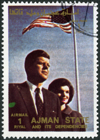 john fitzgerald kennedy: AJMAN - CIRCA 1972: A stamp printed in Ajman shows John F. Kennedy (1917-1963) and wife Jacqueline Lee Jackie Bouvier (1929-1994), series famous mens and women, circa 1972 Editorial
