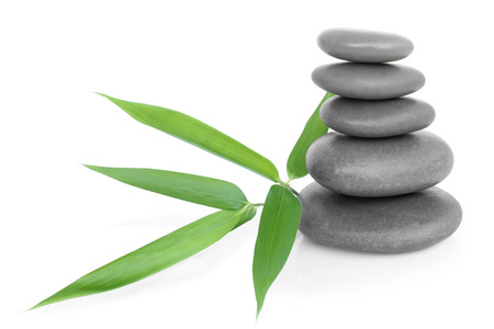 Stacked massage stones and bamboo on white background