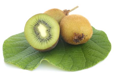actinidia deliciosa: Kiwi fresh fruit with green leaf on white background