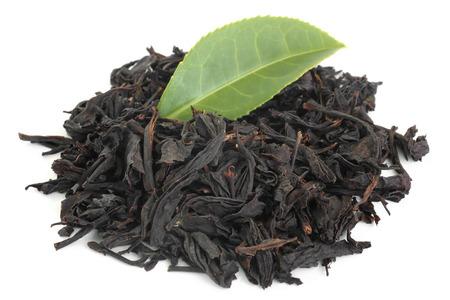Schwarzer Tee mit grünem Tee Blatt auf weißem Hintergrund
