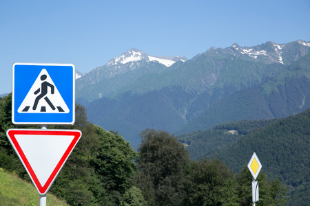 give way: Road signs in a mountain landscape. Pedestrian Crossing, Give Way, and Priority road. Resort Krasnaya Polyana, Sochi, Russia.  Stock Photo