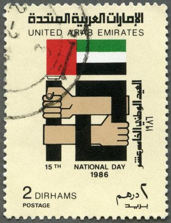 UAE - CIRCA 1986: A stamp printed in United Arab Emirates UAE shows Emblem, 15th National Day, circa 1986