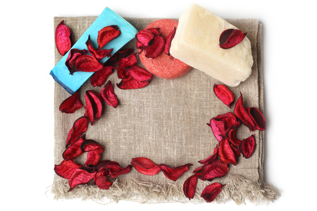Spa composition with toilet soap with dry red petals on canvas fabric, on white background  Stock Photo