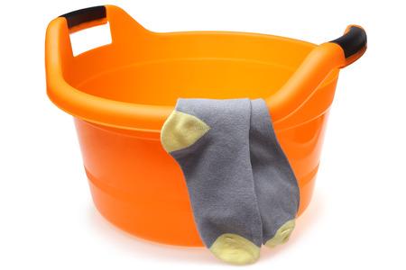 Orange plastic wash bowl with socks on white background