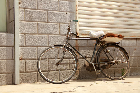 Rusty old bicycle leaning against brick wall