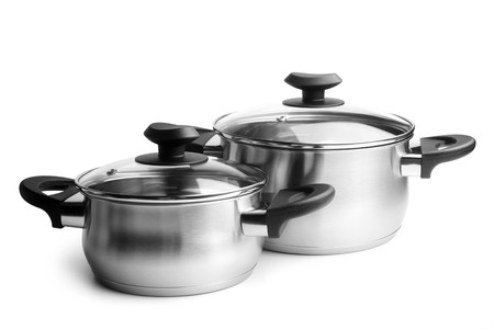 Stainless steel pans with glass lids on white background