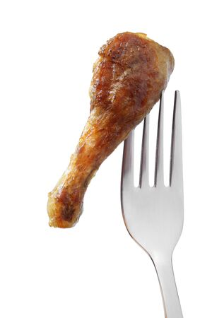 Barbecued chicken leg on a fork isolated on white background
