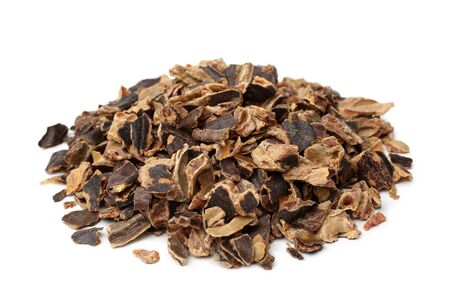 Raw carob kibble nibbles on white background