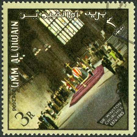 UMM AL-QUWAIN - CIRCA 1965: A stamp printed in Umm al-Quwain shows Sir Winston Leonard Spencer Churchill (1874-1965), coffin, St Paul Cathedral, London, memoreal state funeral, circa 1965