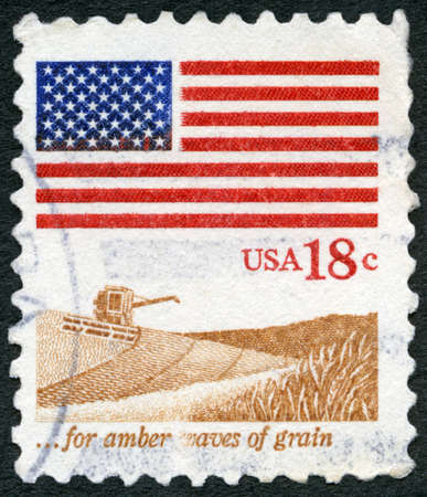 USA - CIRCA 1981: A stamp printed in the USA shows an American Flag, Wheat Fields and harvester, for amber waves of grain, circa 1981 新闻类图片