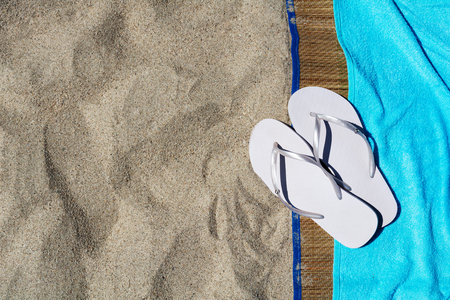 flip flops: Womens flip flops and towel on the beach in the summer