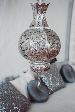 Arab lamps. Moroccan silver lantern on the background of sofa with pillows