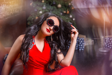 A beautiful, charming girl with sunglasses and a red dress. On the background of a New Year tree