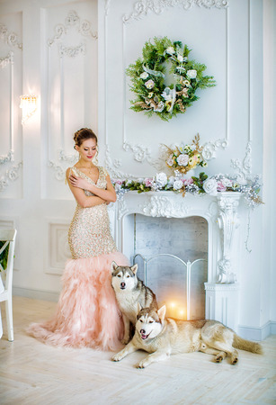 Beautiful young girl in a pink dress standing by the fireplace with a husky dog, on a background of a white luxurious room